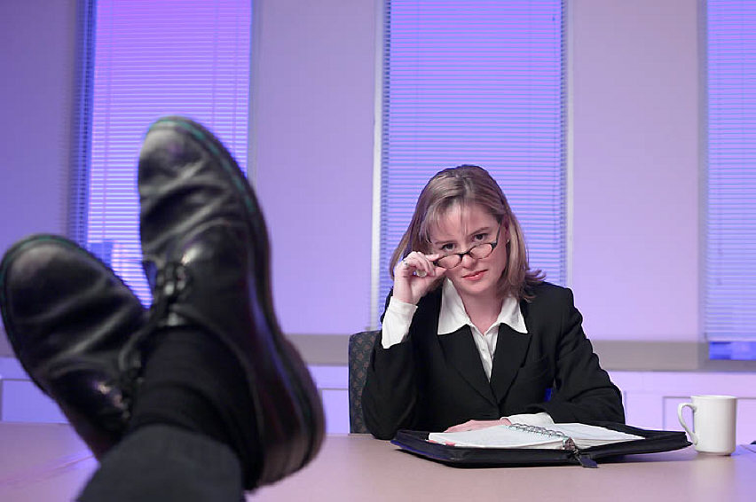 Unimpressed businesswoman at meeting with man feet on desk
