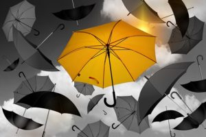 golden umbrella among black and white umbrellas